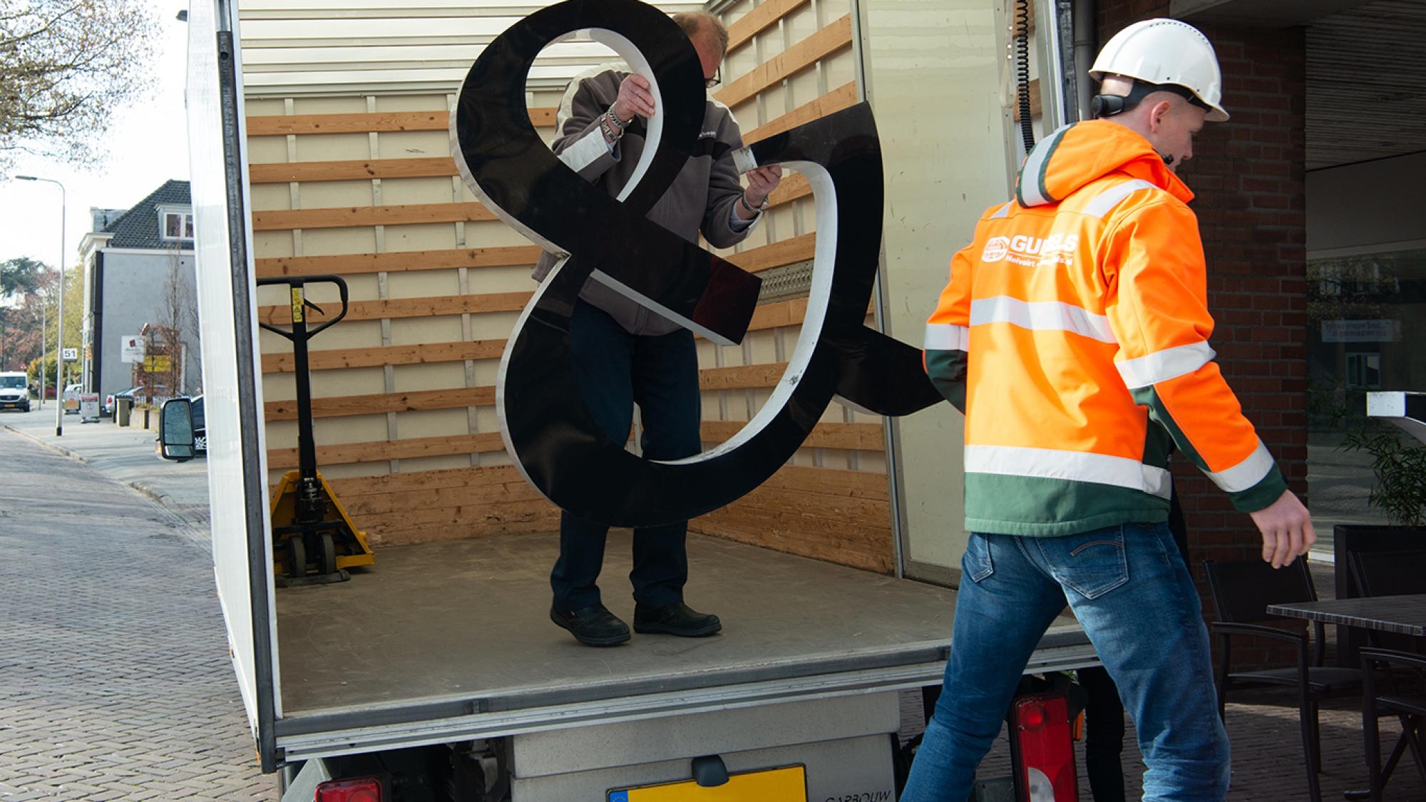 Letters van het logo worden in de bus geladen