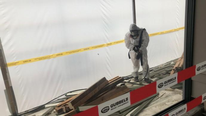 Man in een pak om asbest te verwijderen