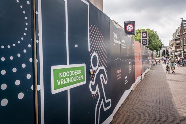 Een deel van de bouwafrastering, hierop staat geschreven: Nooddeur vrijhouden.